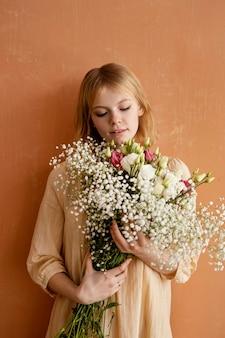 Vista frontale della donna che tiene il mazzo di bellissimi fiori primaverili
