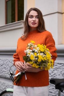 Vista frontale della donna che tiene il mazzo di fiori accanto alla bicicletta