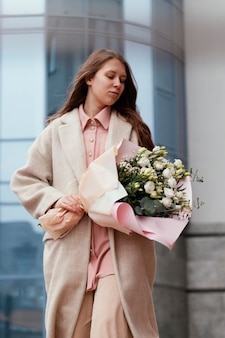 Front view of woman holding bouquet of flowers outdoors