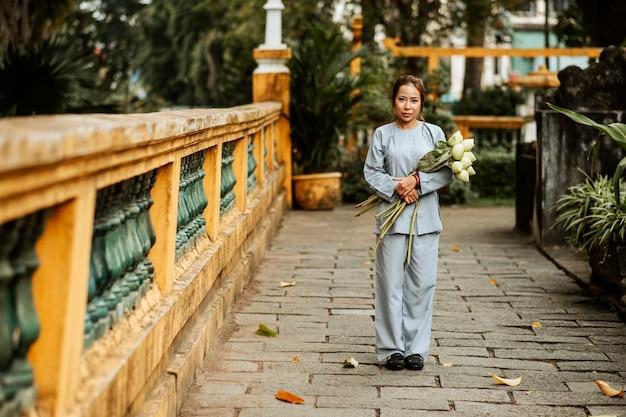 Vista frontale della donna che tiene il mazzo di fiori al tempio
