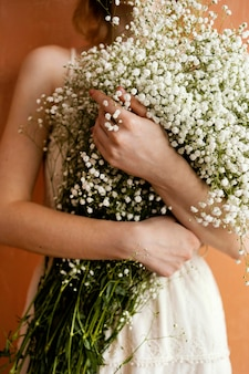 Front view of woman holding bouquet of flowers