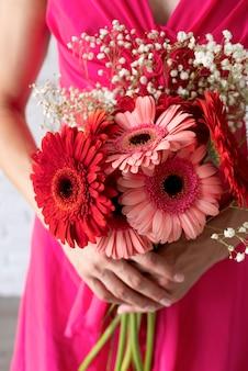 Vista frontale della donna che tiene il mazzo di fiori