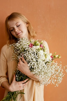 Front view of woman holding bouquet of spring flowers