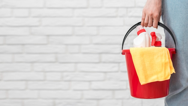 Front view of woman holding bucket with cleaning supplies and copy space