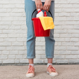 Front view of woman holding bucket with cleaning supplies