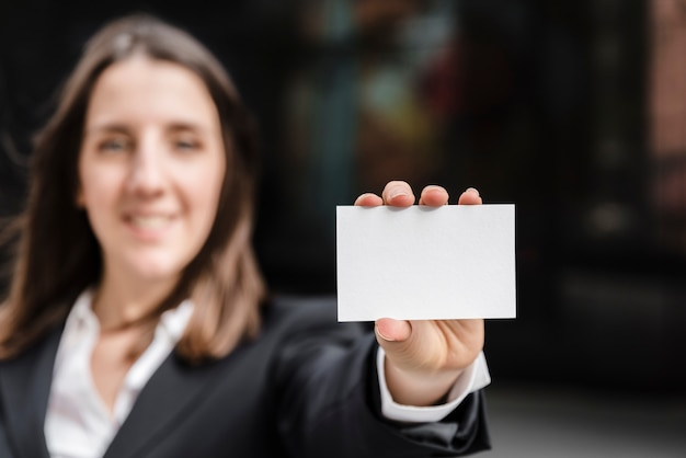 Front view woman holding a business card