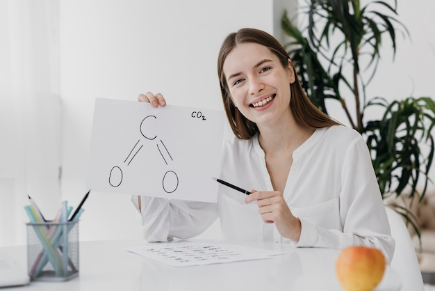 Front view woman holding a chemistry drawing