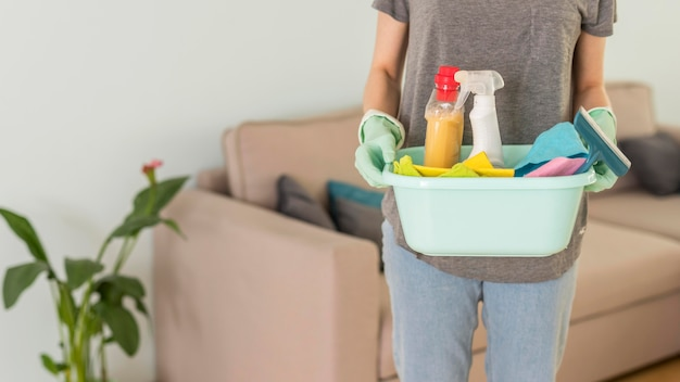 Front view of woman holding cleaning supplies in bucket