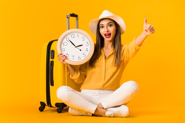 Front view of woman holding clock and giving thumbs up