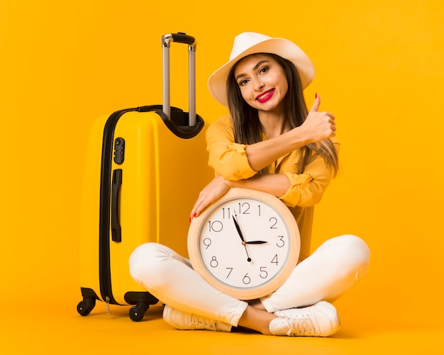 Front view of woman holding clock and posing next to luggage