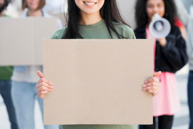 Front view woman holding copy space cardboard