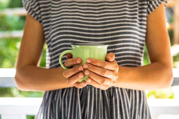 Front view woman holding cup of coffee