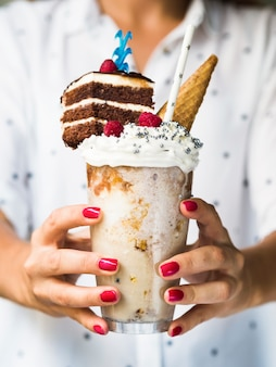 Front view of woman holding delicious milkshake