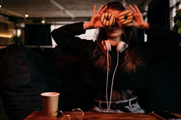 Вид спереди женщина, держащая пончики