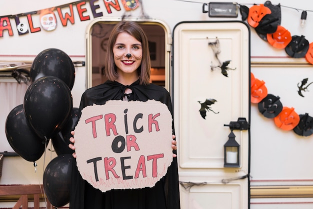 Front view woman holding halloween sign
