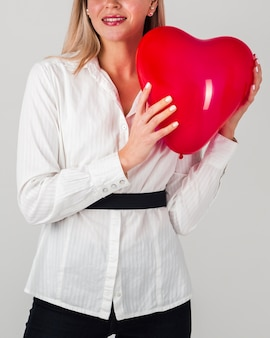 Front view of woman holding heart balloon