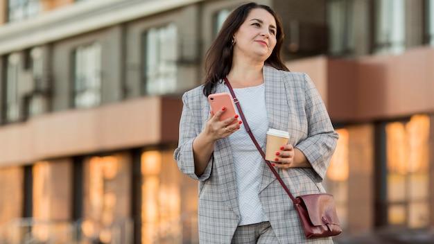 Вид спереди женщина, держащая ее телефон с копией пространства