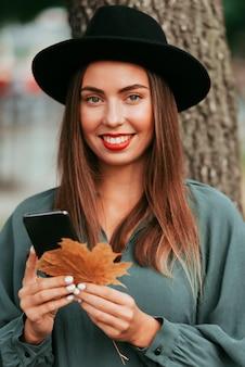 Вид спереди женщина, держащая ее телефон