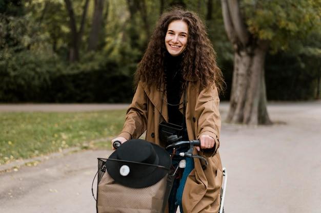 Вид спереди женщина, держащая сумочку на велосипеде