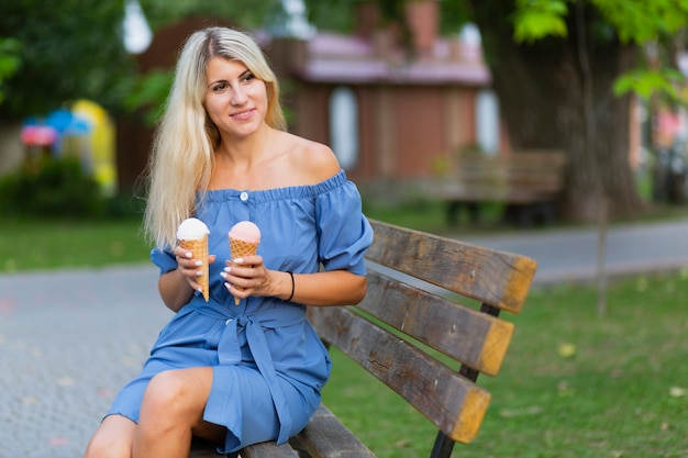 Front view of woman holding ice cream cones