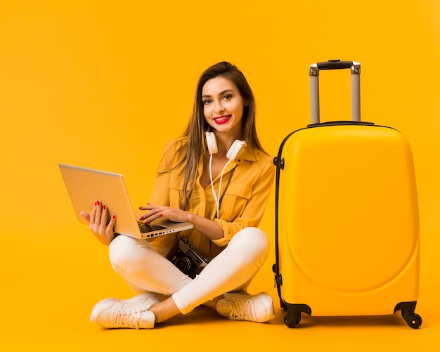 Front view of woman holding laptop and posing next to luggage