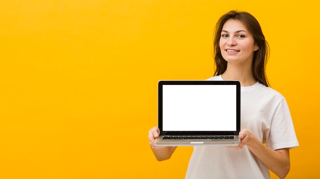 Front view of woman holding laptop with copy space