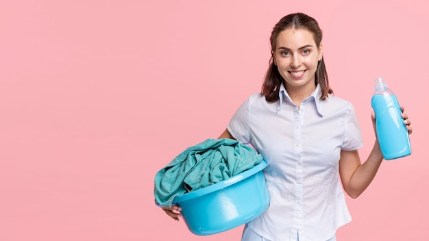Front view woman holding laundry basket and detergent