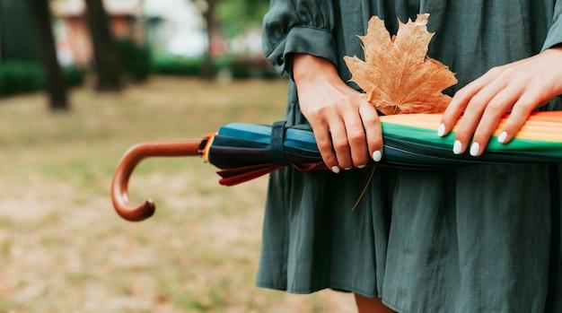 Вид спереди женщина, держащая листья и красочный зонтик с копией пространства