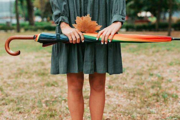 Вид спереди женщина, держащая листья и красочный зонтик