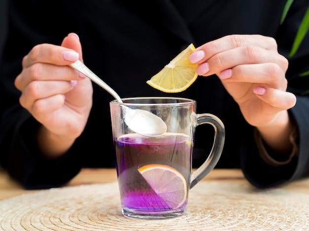 茶碗から小さじ1杯を取ってレモンスライスを保持している正面図女性