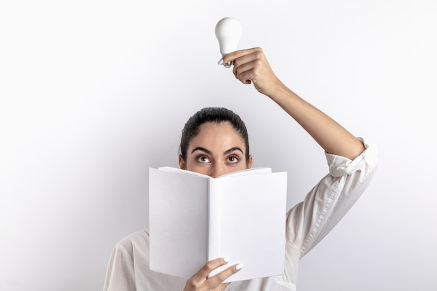 Front view of woman holding light bulb and book