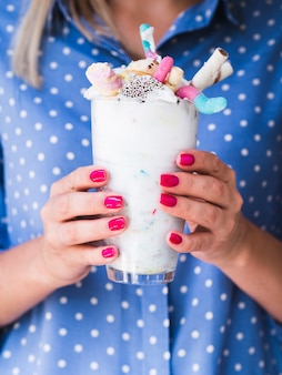 Front view of woman holding a milkshake glass