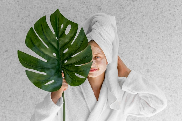 Front view woman holding monstera leaf
