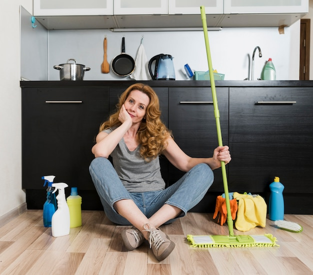 Front view of woman holding mop with cleaning products