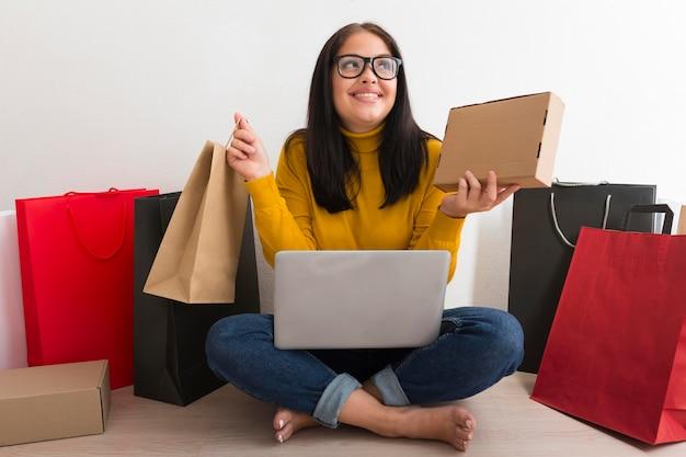 サイバー月曜日の販売からの新しいパッケージを保持している正面図女性