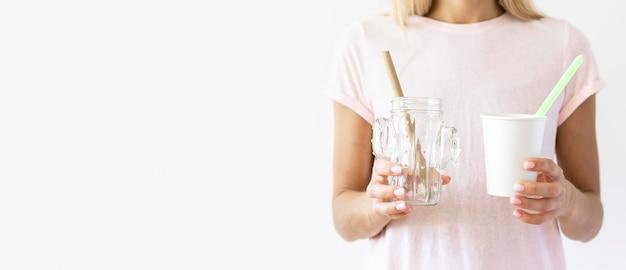 Вид спереди женщина, держащая пластиковые стаканчики с копией пространства