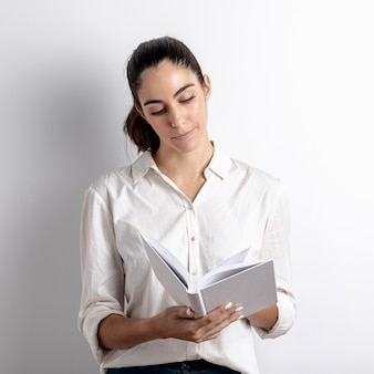 Front view of woman holding and reading book
