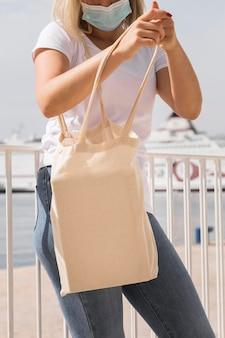 Donna di vista frontale che tiene borsa riciclabile