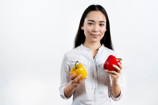 Vista frontale della donna che tiene peperone rosso e giallo che si leva in piedi davanti alla priorità bassa isolata