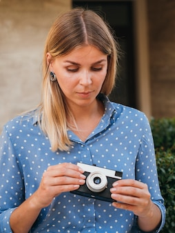 Front view woman holding a retro photo camera