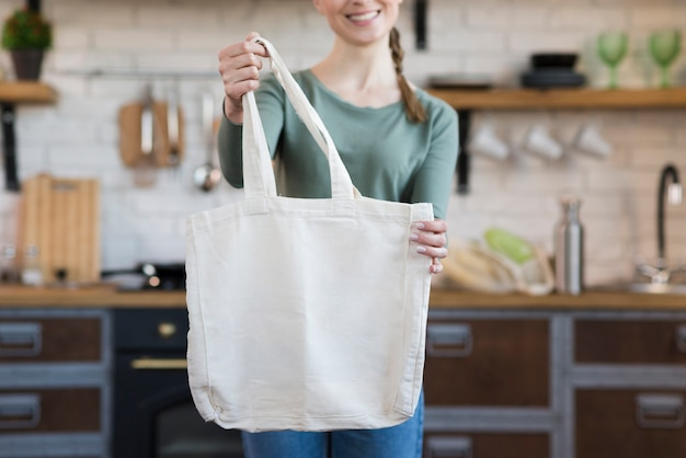 Front view woman holding reusable groceries bag