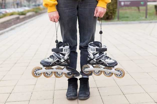 Front view of woman holding roller blades in each hand