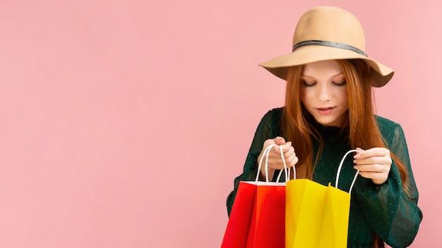 買い物袋を保持している正面図女性