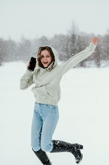 Front view of woman holding smartphone and jumping in the air outdoors