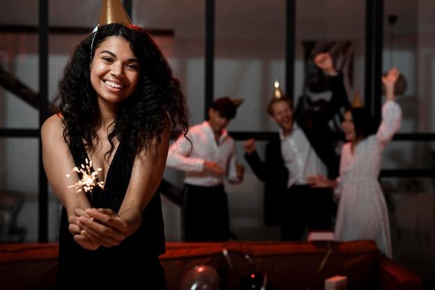 コピースペースで大晦日のパーティーで線香花火を保持している正面図の女性