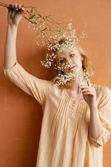 Vista frontale della donna che tiene i fiori di primavera