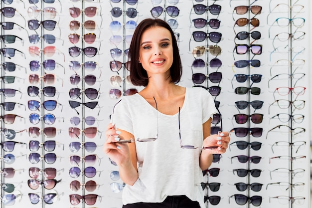 Front view of woman holding sunglasses pairs