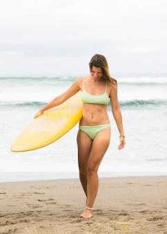 Vista frontale della donna che tiene la tavola da surf in spiaggia