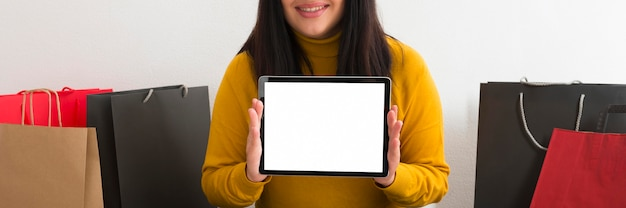 Front view woman holding a tablet with an empty screen