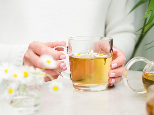 ガラスでお茶を保持している正面図女性